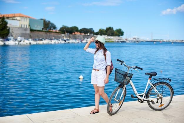 Ragazza attraente felice in occhiali da sole e con zaino in sella a una bicicletta lungo marciapiede pietroso Foto Premium