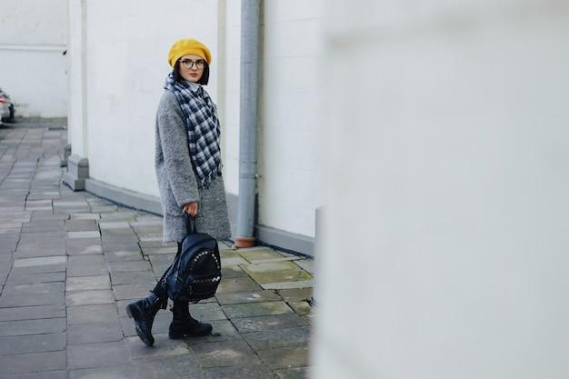 Ragazza attraente in vetri nel cappotto e nella camminata gialla di stile libero del berretto Foto Premium