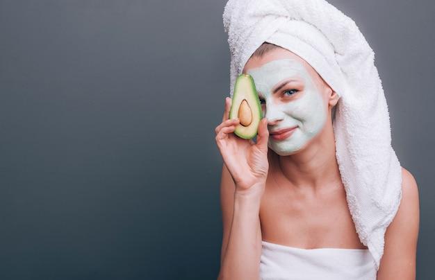 Ragazza avvolta in un asciugamano con una maschera cosmetica sul viso e avocado nelle sue mani Foto Premium
