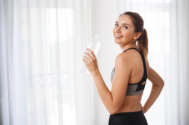 Ragazza bella fitness con bottiglia d'acqua davanti alla finestra Foto Gratuite