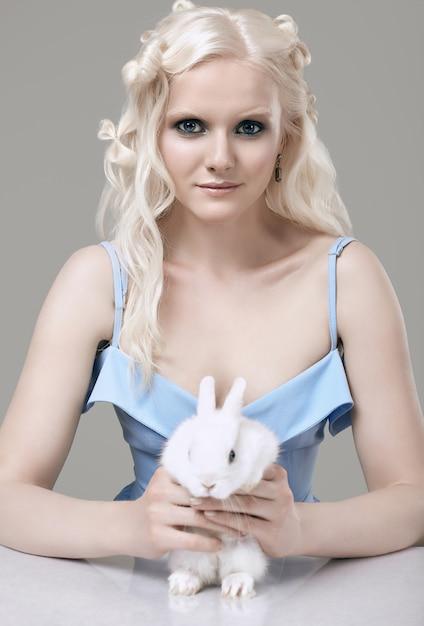 Ragazza bionda albina in abito elegante in posa con simpatico coniglietto Foto Premium