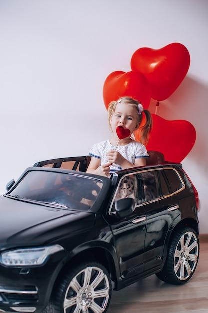 Ragazza bionda che mangia un caramello lollypop a forma di cuore. scherzi la seduta in un'automobile nera del giocattolo con i palloni a forma di cuore rosso. concetto di san valentino. Foto Premium