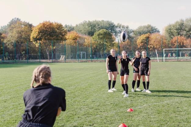 Ragazza bionda che passa un pallone da calcio Foto Gratuite