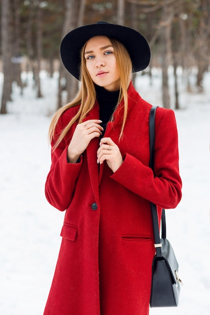 Ragazza bionda che porta cappotto rosso su un campo nevoso Foto Gratuite