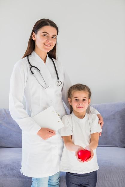 Ragazza bionda che tiene il cuore con il medico Foto Gratuite