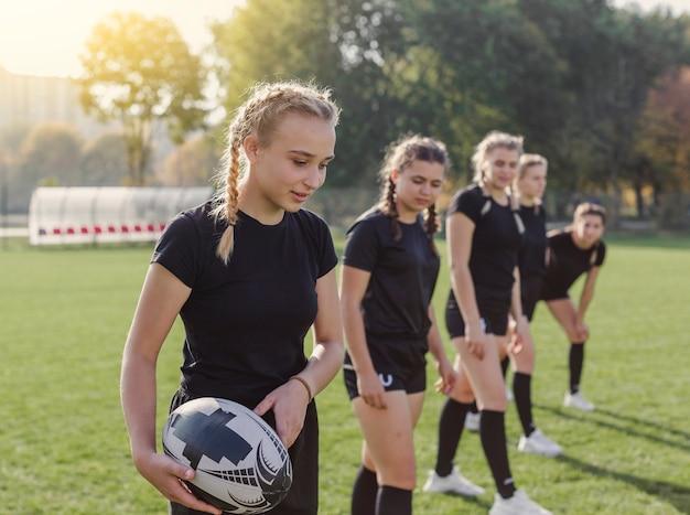 Ragazza bionda che tiene una palla di rugby Foto Gratuite