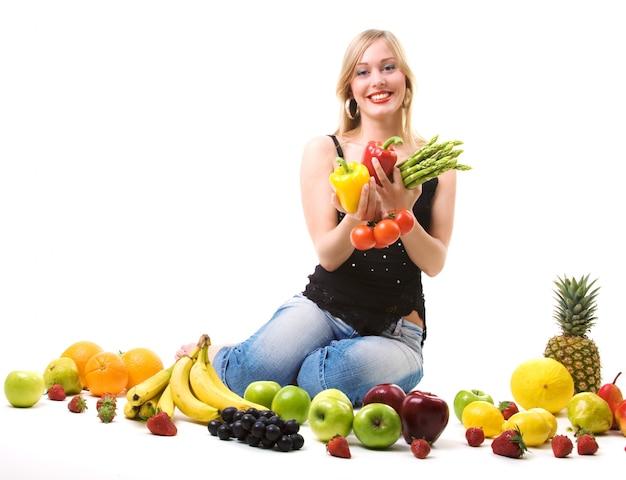 Ragazza bionda circondata da frutta e verdura Foto Premium