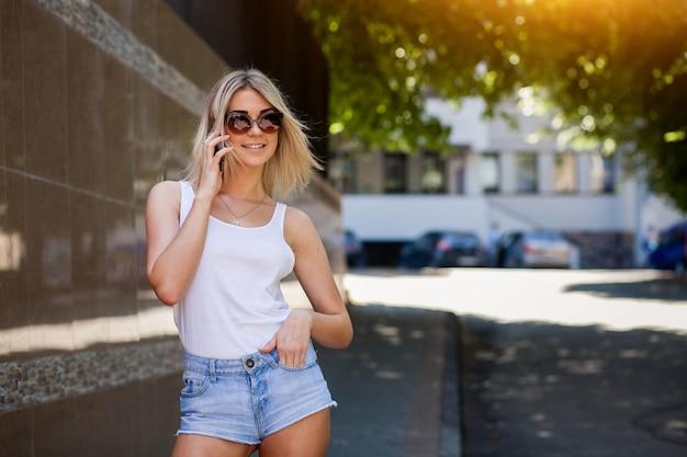 88fb1a036135ed Ragazza bionda con gli occhiali da sole a parlare al telefono ...