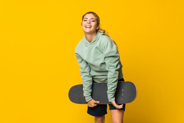 Ragazza bionda del pattinatore dell'adolescente sopra giallo isolato Foto Premium