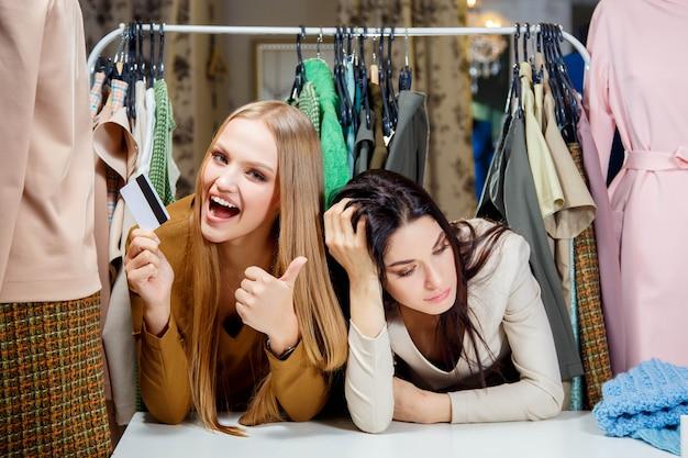Ragazza bionda felice che fa spesa con una carta di credito Foto Premium