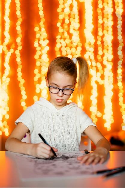Ragazza bionda in abito bianco a maglia e grandi occhiali neri disegno babbo natale. tema del nuovo anno Foto Premium
