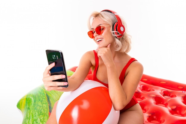 Ragazza bionda in costume da bagno rosso e occhiali da sole seduto sul materasso di nuoto e ascoltando musica in cuffia e con in mano uno smartphone Foto Premium