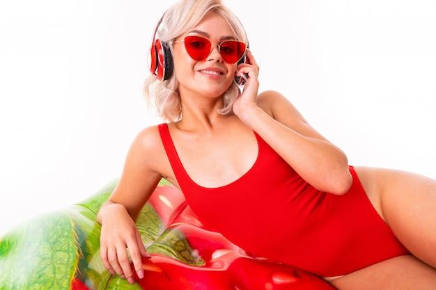 Ragazza bionda in costume da bagno rosso e occhiali da sole si trova sul materasso nuoto e ascolta la musica in cuffia Foto Premium