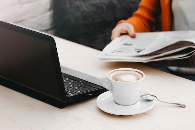 Ragazza bionda in un caffè con un computer portatile e caffè. free lance della ragazza che lavorano ad un computer portatile Foto Premium
