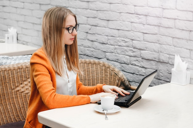 Ragazza bionda in un caffè con un computer portatile e una tazza di caffè. free lance della ragazza che lavorano ad un computer portatile Foto Premium