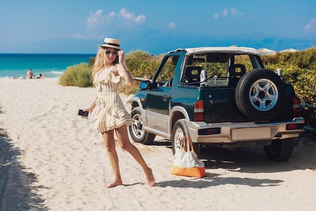 Ragazza bionda in vestito a strisce che posa sulla macchina fotografica sulla spiaggia sabbiosa Foto Premium