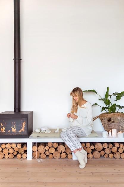 Ragazza bionda lavora a maglia seduta su un cuscino accanto al camino in un accogliente interno scandinavo Foto Premium