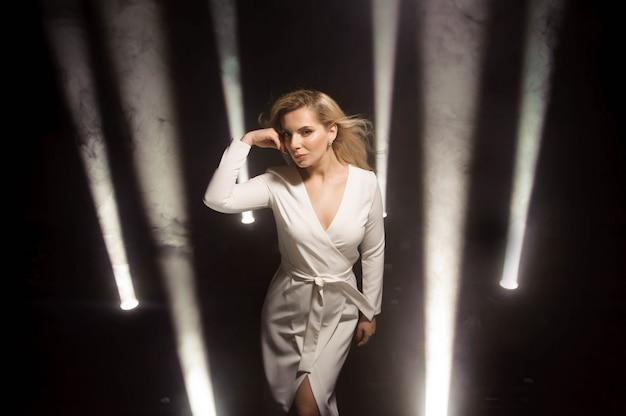 Ragazza bionda moda con capelli ricci lunghi e lucenti. bellissima modella in abito bianco sul palco con luci. Foto Premium