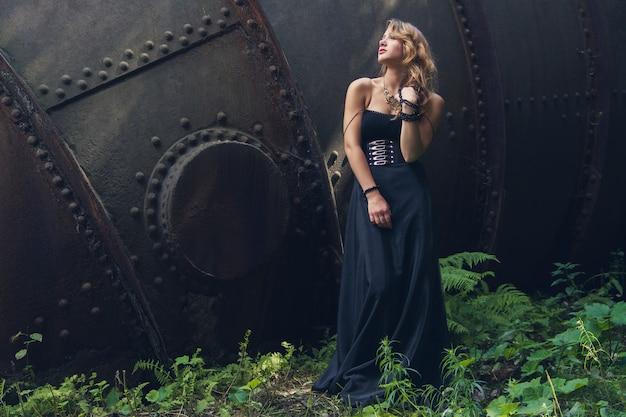 Ragazza bionda nella vecchia fabbrica abbandonata del vestito nero Foto Premium