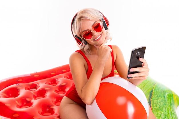 Ragazza bionda sorridente in un costume da bagno rosso e occhiali da sole seduto sul materasso di nuoto e ascoltando musica in cuffia e tenendo un telefono in mano Foto Premium
