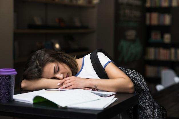 Ragazza bruna che dorme appoggiata sul tavolo Foto Gratuite