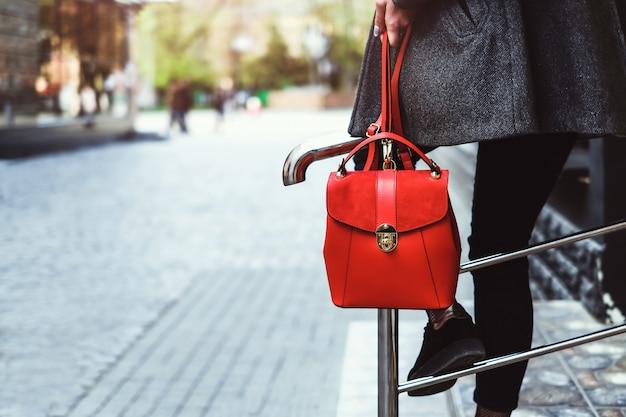 Ragazza bruna che si siede sulla barriera con lo zaino rosso Foto Premium