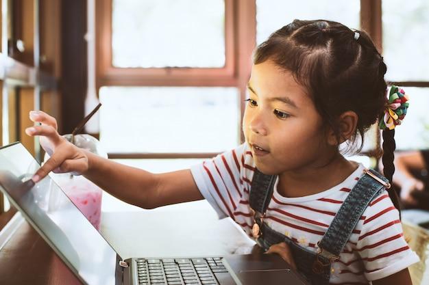 Ragazza carina asiatica bambino utilizzando e giocando sul portatile nel caffè con divertimento e felicità Foto Premium