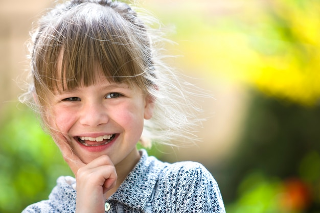 Ragazza carina bambino carino con occhi grigi e capelli biondi sorridente Foto Premium