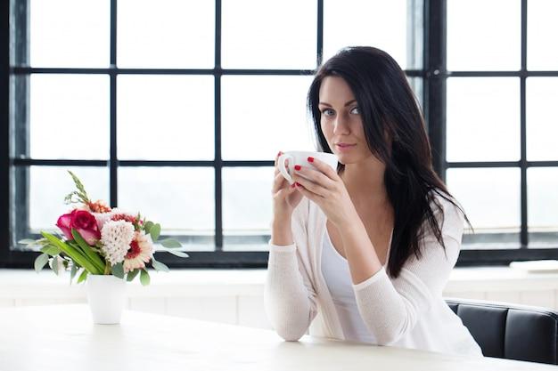 Ragazza carina con caffè Foto Gratuite