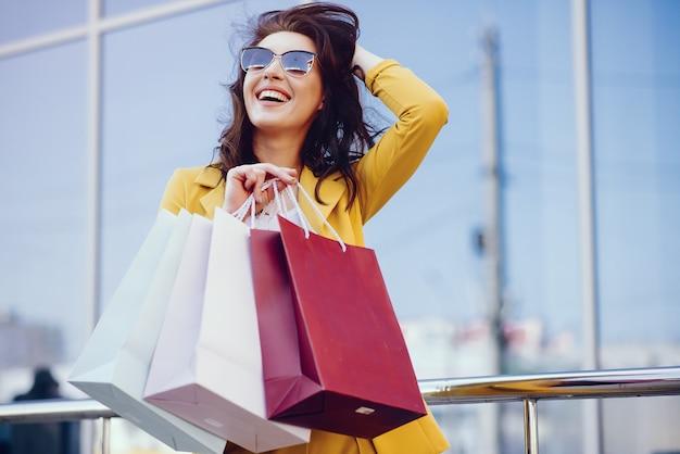 Ragazza carina con shopping bag in una città Foto Gratuite