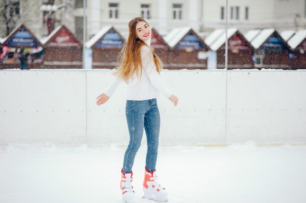 Ragazza carina e bella in un maglione bianco in una città d'inverno Foto Gratuite