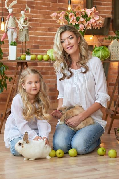 Ragazza carina e madre che giocano con i conigli Foto Premium