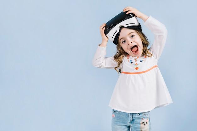 Ragazza carina felice con auricolare virtuale sulla sua testa su sfondo blu Foto Gratuite