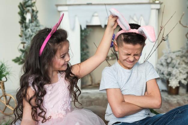 Ragazza carina guardando ragazzo offeso nelle orecchie di coniglio Foto Gratuite