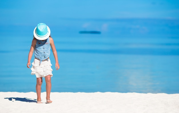 Ragazza carina in cappello in spiaggia durante le vacanze estive Foto Premium