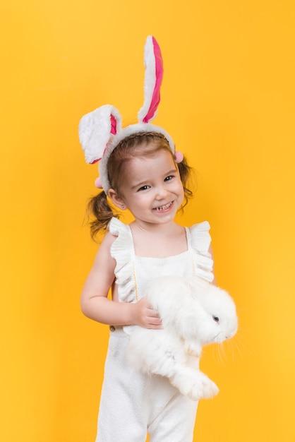 Ragazza carina in orecchie da coniglio con coniglio Foto Gratuite