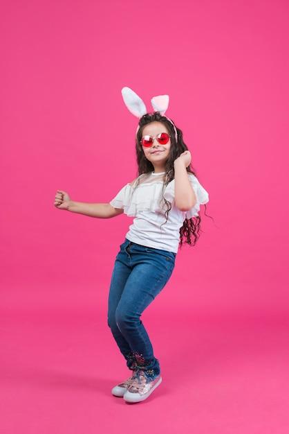 Ragazza carina in orecchie da coniglio danza Foto Gratuite