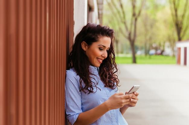 Ragazza carina in piedi accanto al muro e mandare sms Foto Premium