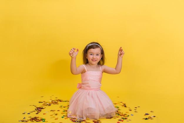 Ragazza carina in un vestito gonfio rosa è seduta e gioca con i coriandoli. festa di compleanno. Foto Premium