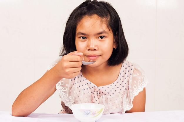 Ragazza carina mangiando cereali per la colazione Foto Premium