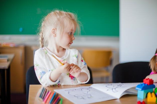 Ragazza carina seduta al tavolo in classe Foto Gratuite