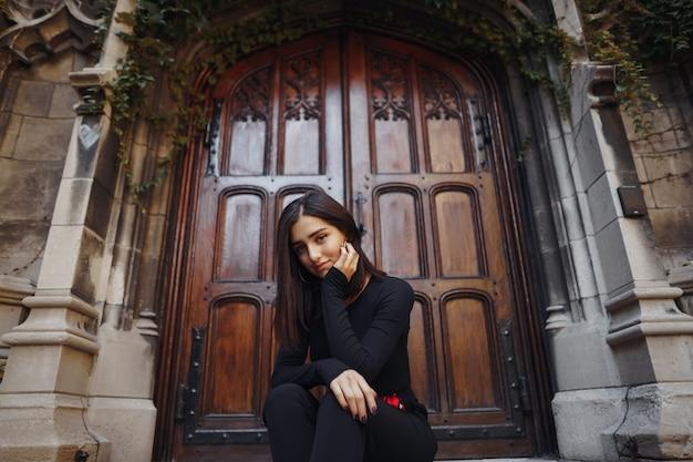 Ragazza castana alla moda che si siede sulle scale Foto Gratuite