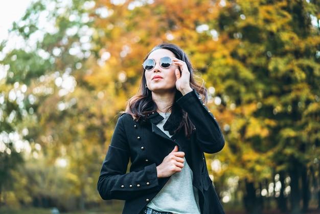 Ragazza castana dei capelli abbastanza lunghi che si rilassa nel parco Foto Premium