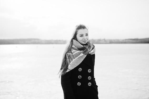 Ragazza casuale al cappotto nero e sciarpa contro il fiume congelato sul tempo soleggiato di inverno. Foto Premium