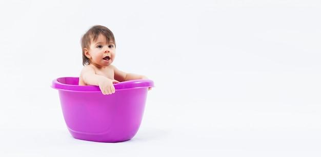 Ragazza caucasica adorabile che prende bagno in vasca porpora su fondo bianco Foto Premium