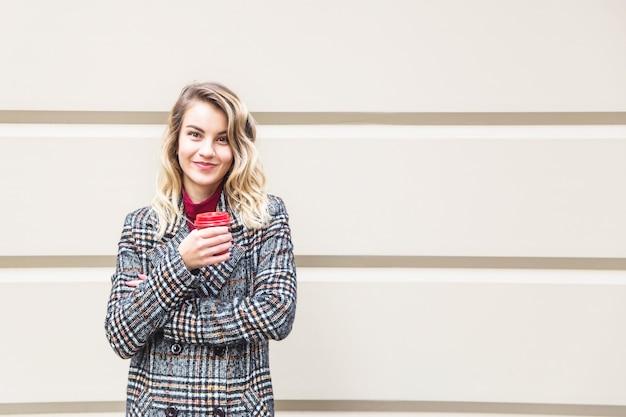 Ragazza caucasica che tiene una tazza rossa con caffè da andare. Foto Premium
