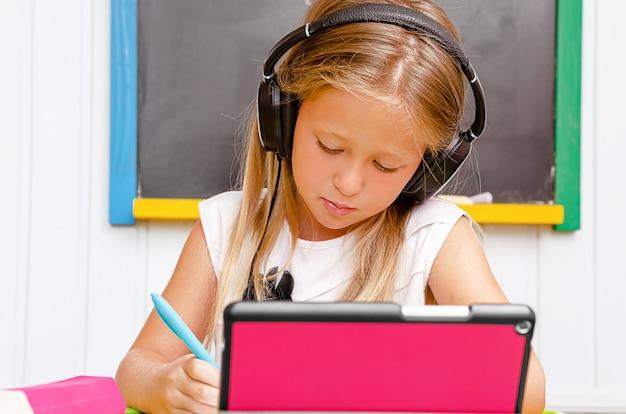 Ragazza caucasica con le cuffie che ascolta e che scrive. istruzione domestica e istruzione a distanza Foto Premium