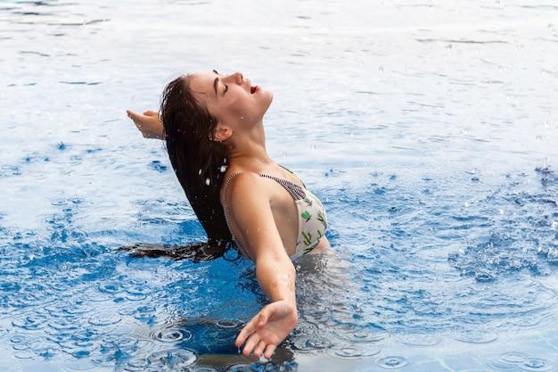 Ragazza caucasica di bellezza che spruzza acqua con i suoi capelli nello stagno. Foto Premium
