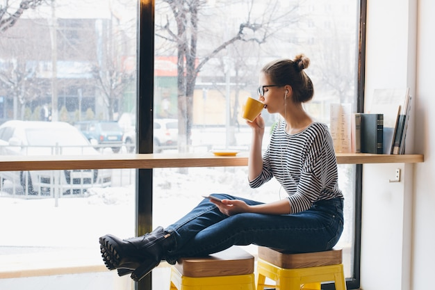 Ragazza che ascolta la musica sul tuo smartphone e che beve caffè Foto Premium
