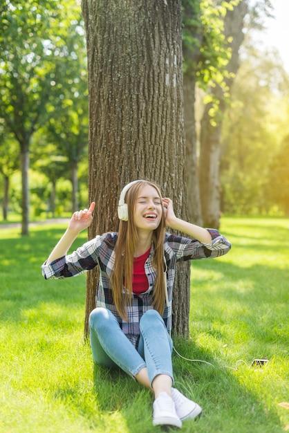 Ragazza che ascolta la musica sulle cuffie bianche Foto Gratuite